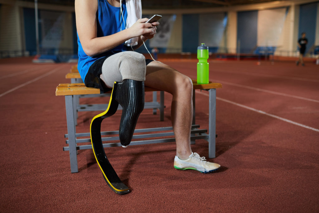 Person in athletic wear sitting down on bench with a prosthetic leg